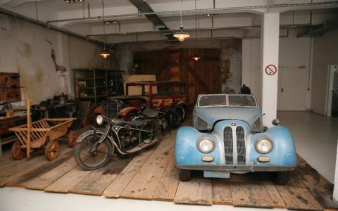 Unrestored cars at the BMW Klassik warehouse, including a 327 convertible.