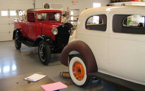 Vehicles wait in the Gilmore Museum's restoration workshop.