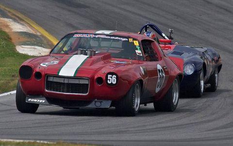 A 1970 Chevrolet Camaro powers through turn 1 ahead of an E-type Jaguar.