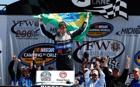Nelson Piquet Jr. celebrates in victory lane.