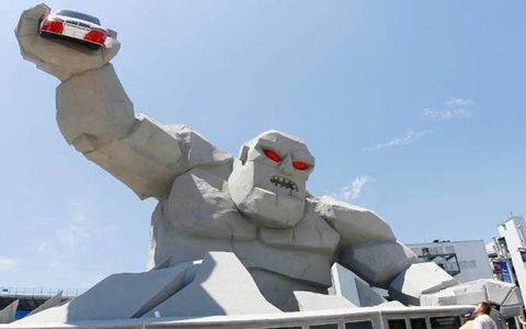 The newly constructed Monster Monument at Victory Plaza stands 46 feet tall and holds a full scale NASCAR COT car in his right hand.