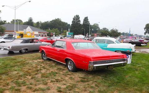 A 1964 GTO and a 1955 Bel Air are parked roadside.