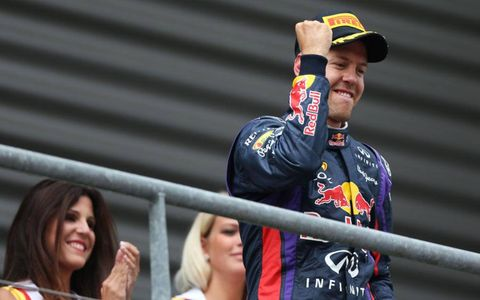 Sebastian Vettel throws a fist in the air from the podium in Belgium.