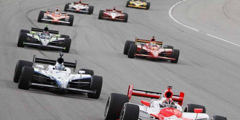 Helio Castroneves leads Marco Andretti, Justin Wilson and Helio Castroneves as he works his way up through the pack