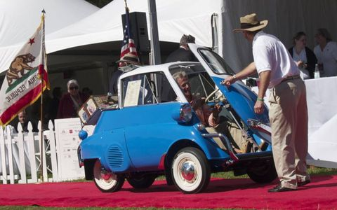 """Hillsborough Concours chairman Rob Fisher opens the Isetta door to present the """"People's Choice"""" award. The student-built car also won the """"Chairman's Award."""""""