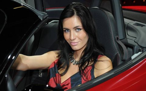 Visitors of the Frankfurt auto show are never disappointed by the beauty of both the cars and the girls that garnish them. Here a car booth model shows off a red convertible.
