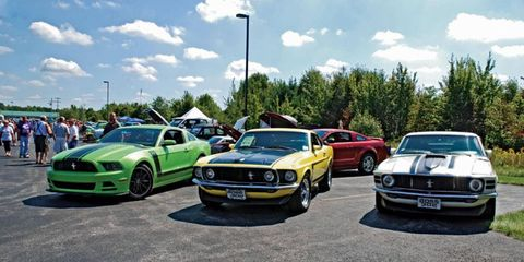A collection of Boss 302's. From left to right, a 2013, 1969 and 1970 pose for photos.
