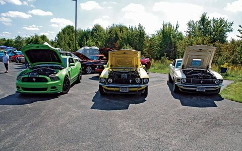 The trio of Ford Mustang Boss 302's at a car show.