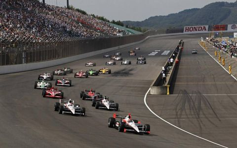Helio Castroneves leads the field into turn one at the start.