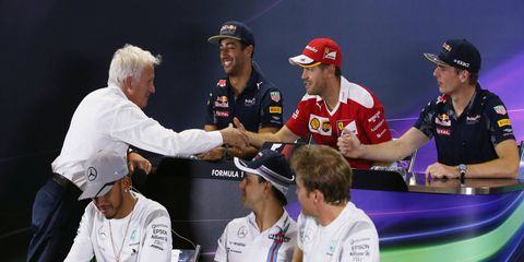 Race director Charlie Whiting, left, and Sebastian Vettel shake hands during a press gathering in Brazil on Thursday.