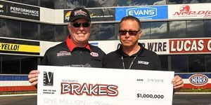 Former NHRA Top Fuel pilot Doug Herbert, left, accepts a $1 million donation on Saturday at Pomona from NHRA motorcycle great Terry Vance for Herbert's foundation.