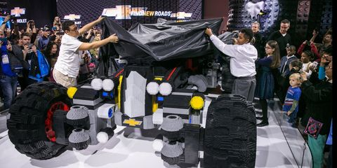 Workers take the wraps off the Batmobile at the Detroit auto show.