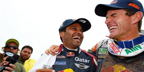 Nasser Al-Attiyah (right) celebrates his Dakar victory with Spain's Coma Marc, who won the Dakar Rally's motorcycle title.