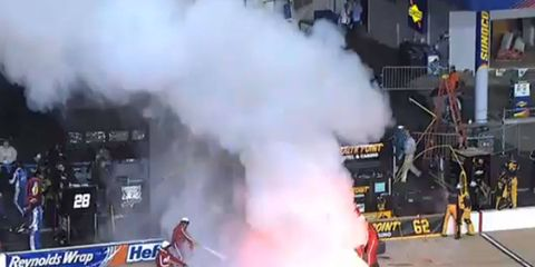 Emergency personnel battle a fire in the pits during the NASCAR Xfinity Series race on Friday night in Richmond, Va.
