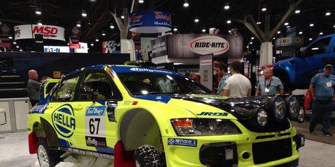 An old Mitsubishi Evo hatchback with Hella rally lights.