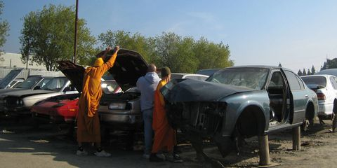 Buddhist monks pulling parts from an Infiniti Q45