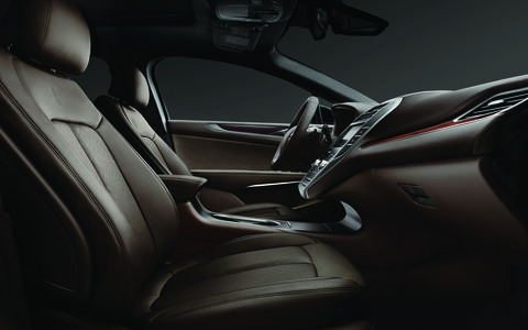 The cabin of the Lincoln MKC featuring the Indulgence Black Label design theme with rich browns, seat leather with a linking-L pattern with black accent stitching and Ziricote wood trim.