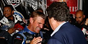 Clint Bowyer shakes hands with NASCAR vice chairman Mike Helton after winning the Monster Energy NASCAR Cup Series FireKeepers Casino 400.