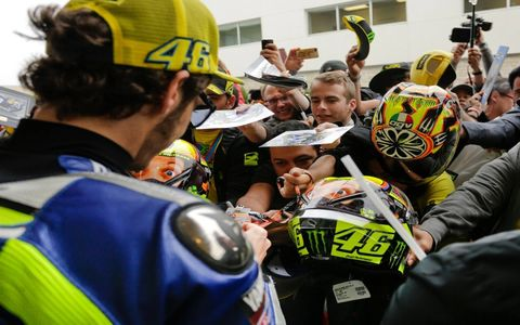 Fans in the paddock fight for the chance to get an autograph from multiple-time world champion Valentino Rossi. Oddly enough, Rossi and a few of his team members were at the rent-a-car counter late Wednesday night at the same time I was -- no one was around -- and perhaps i was the only one who even recognized him. Super friendly guy in that situation.