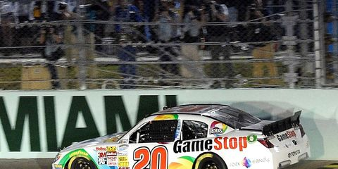 Matt Kenseth crosses the finish line after passing Kyle Larson on a restart as part of a green-white-checkered finish at Homestead-Miami Speedway on Saturday night.
