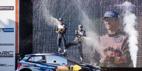 Sébastien Ogier and co-driver Julien Ingrassia celebrate on the podium after winning the FIA World Rally Championship in Coffs Harbour, Australia, on Sept. 13.