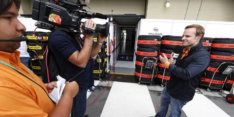 Rubens Barrichello, right, served as a roving reporter for a Brazilian TV station at the Singapore Grand Prix.