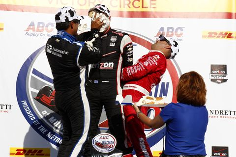 Will Power, center, is creamed with cream puffs by teammate Juan Pablo Montoya, left, and Tony Kanaan on the podium Sunday.