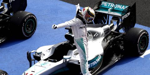 Lewis Hamilton celebrates as he jumps from his car in parc fermé after winning the Mexican Grand Prix