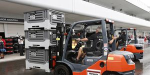 Lotus F1 workers scramble to set up shop after their equipment arrived late in Japan.
