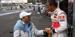 Philippe Streiff talks with Formula One champion Lewis Hamilton in 2009.