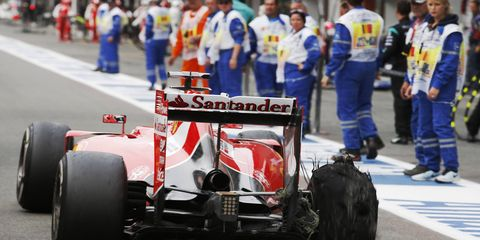 Sebastian Vettel's Ferrari limps into the pits after blowing a tire at Spa.