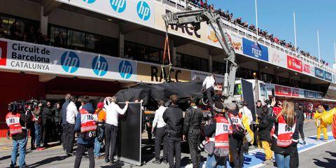 Fernando Alonso's McLaren-Honda Formula One car is hauled into the garage under wraps following Sunday's crash.
