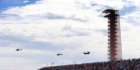 A pair of US Army AH-64D Longbow Apache helicopters escort a CH-47D Chinook as part of the pre-race grid celebrations.