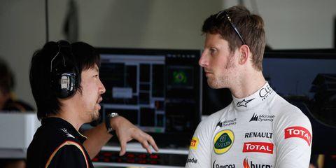 Chief engineer and team strategist Ayao Komatsu, left, talks shop with Haas F1 Team driver Romain Grosjean.