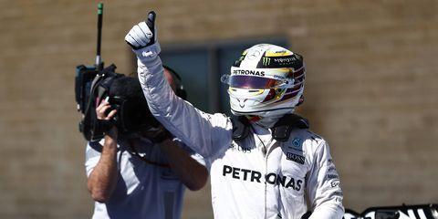 Lewis Hamilton celebrates in parc fermé after taking pole position
