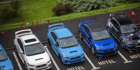 The Subaru WRX STI Type RA (dark blue) parked next to its STI brothers.