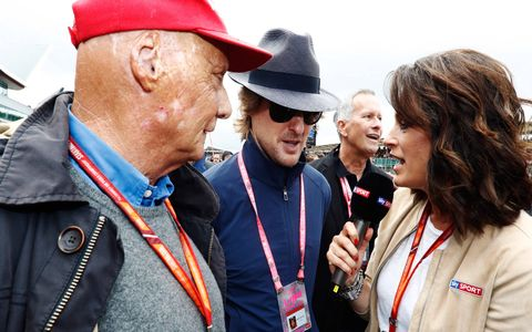 Owen Wilson, center, visits pit lane prior to the race.