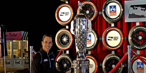 Helio Castroneves points to his likeness on the Borg-Warner Trophy on Friday at the Detroit auto show.