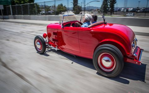 Autoweek contributor Jay Leno drives Bruce Meyer's McGee roadster, one of two cars featured on a USPS stamp.