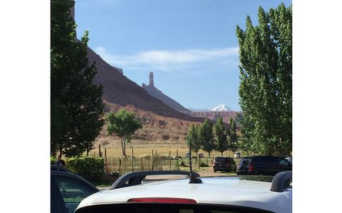 That's Castleton Tower poking up above the roof of a Jeep Cherokee Trailhawk.