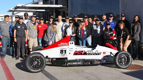 Feustel, Lyn St. James and RPM President Diane Fitzgerald and group of students with Feustel's race car.