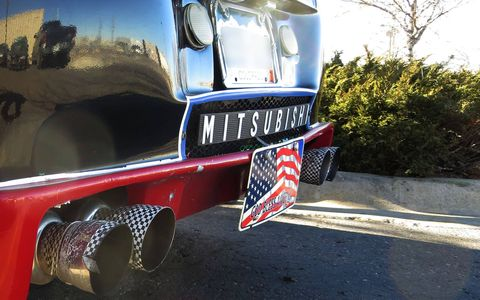 Patriotic second license plate, checkered-flag tape on the tailpipes, and a big MITSUSBISHI sign.