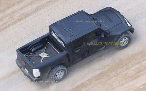 The 2019 Jeep Wrangler pickup is spotted for the first time, undergoing testing. Yes, that looks like a Ram pickup bed.
