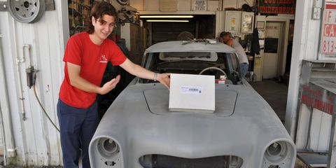 Kyle Feller, youngest member of the Mercury restoration team, poses with the Pebble Beach Concours d'Elegance entrant's packet. The car has a ways to go before the show, but at least the paperwork is in order.