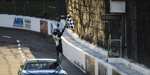 Jimmie Johnson celebrates his win at Martinsville Speedway with the checkered flag.