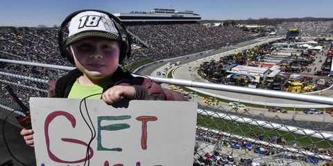 """A young NASCAR fan holds up a """"get well soon"""" card for Kyle Busch. Busch was injured in a wreck at Daytona earlier this year."""