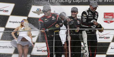 Third-place finisher Juan Pablo Montoya, left, race winner Will Power, center, and runner-up Graham Rahal celebrate on the podium after Saturday's Grand Prix of Indianapolis at the Indianapolis Motor Speedway.