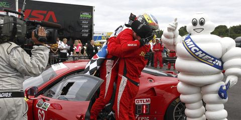 Giancarlo Fisichella and Pierre Kaffer embrace after winning the GTLM race in Virginia.