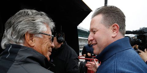 Mario Andretti, left, and McLaren executive director Zak Brown chat during a practice session at Indianapolis.