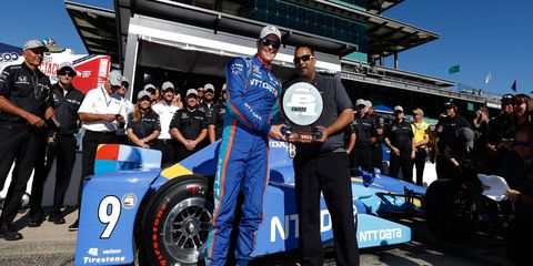 Scott Dixon receives his pole award at Indianapolis on Sunday.
